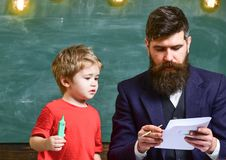 Child and teacher on busy face painting, drawing. Teacher with beard, father teaches little son to draw in classroom. Chalkboard on background. Art lesson royalty free stock image