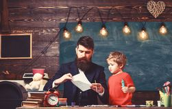 Child and teacher on busy face painting, drawing. Talented artist spend time with son. Teacher with beard, father. Teaches little son to draw in classroom royalty free stock photography