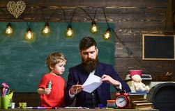 Child and teacher on busy face painting, drawing. Talented artist spend time with son. Teacher with beard, father. Teaches little son to draw in classroom royalty free stock images