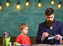 Child and teacher on busy face painting, drawing. Teacher with beard, father drawing while little son hang out near, in. Classroom, chalkboard on background stock photography