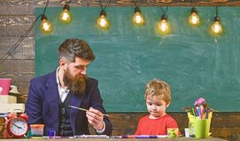 Child and teacher on busy face painting, drawing. Teacher with beard, father teaches little son to draw in classroom. Chalkboard on background. Art lesson stock photo