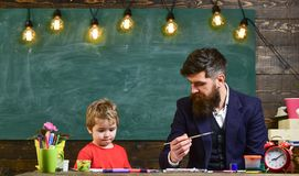 Child and teacher on busy face painting, drawing. Teacher with beard, father teaches little son to draw in classroom. Chalkboard on background. Art lesson stock images