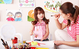 Child with teacher draw paints in play room. Royalty Free Stock Photos