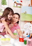 Child with teacher draw paints in play room. Royalty Free Stock Photography