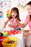 Child with teacher draw paints in play room. Stock Photos