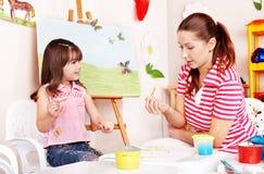 Child with teacher draw paints in play room. Preschooler stock image
