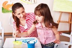 Child with teacher draw paints in play room. Preschooler stock photos