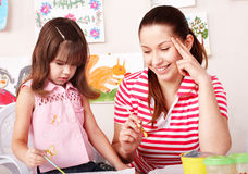 Child with teacher draw paints in play room. Preschool royalty free stock photos