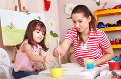 Child with teacher draw paints in play room. Preschool stock photography