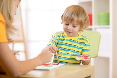 Child with teacher draw paints in play room. Preschool. royalty free stock images