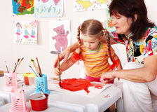 Child with teacher draw paints in playroom. Preschool royalty free stock images
