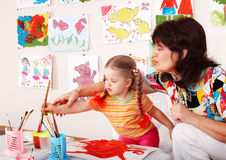 Child with teacher draw paints in playroom. Preschool stock image
