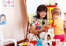 Child with teacher draw paints in playroom. Royalty Free Stock Image