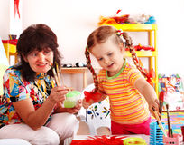 Child with teacher draw paints in playroom. Royalty Free Stock Photos