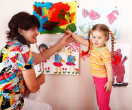 Child with teacher draw paints in playroom. Stock Photos