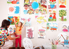 Child with teacher draw paints in playroom. Royalty Free Stock Photo
