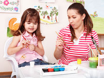 Child with teacher draw  in play room. Royalty Free Stock Photography