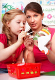 Child with teacher glue in play room. Royalty Free Stock Photography
