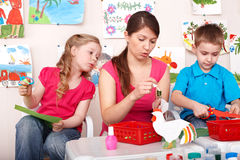 Child with teacher in play room. stock image