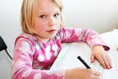 Child teaching. A blonde girl 6 years old teach writing Stock Image