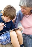Child teaching grandmother how to use tablet stock images