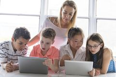 Child with technology tablet and laptop computer in classroom teacher on the background royalty free stock image