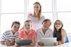 Child with technology tablet and laptop computer in classroom teacher on the background stock photo