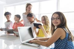Child with technology tablet and laptop computer in classroom teacher on the background royalty free stock photos