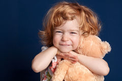 Child and teddy. Smiling beautiful child embraces teddy bear stock photos