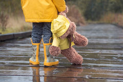 Child and teddy bear in yellow raincoats standing in the rain. Even rain is not a problem if your friend is with you. In childhood everything is an adventure Royalty Free Stock Image