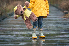 Child and teddy bear in yellow raincoats standing in the rain Stock Photo
