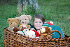 Child with teddy bears. Happy cute little girl surrounded by lots of brown and white teddy bears Stock Photo