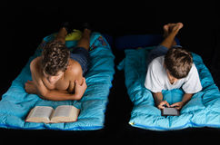 Child and teen boy reading book and ebook Royalty Free Stock Image
