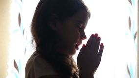 Child teen girl praying prays silhouette in the