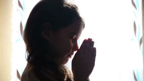 Child teen girl praying prays silhouette in window stock video footage