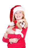 Child or teen holding a dog wearing a Santa hat Stock Photos