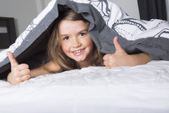 Child or teen under covers in bed Royalty Free Stock Photography
