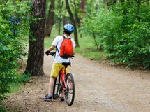 Child teenager on bicycle ride in forest at spring or summer. Happy smiling Boy cycling outdoors in blue helmet. Active lifestyle. Hobby royalty free stock images