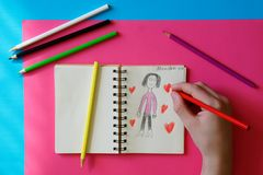 Child - teenager draws a picture for mom stock images
