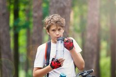 Child teenager in white t shirt and yellow shorts on bicycle ride in forest at spring or summer. Happy smiling Boy cycling royalty free stock photos