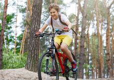 Child teenager in white t shirt and yellow shorts on bicycle ride in forest at spring or summer. Happy smiling Boy cycling royalty free stock image