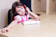Child on telephone in office. Asian child in office talking on telephone Stock Image
