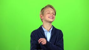 Cild tells the information to others. Green sreen. Slow motion. Child tells the information to others, he is angry and nervous. Green screen. Slow motion stock video footage