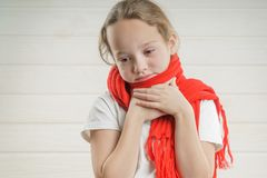 Child temperature. sore throat. bad condition. a child rooting. scarf. The girl is sick royalty free stock photo