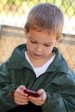 Child Texting. A closeup of a cute little boy texting on the phone and wearing a green jacket. Shallow depth of field Royalty Free Stock Photos