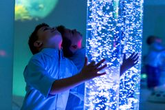 Child in therapy sensory stimulating room, snoezelen. Child interacting with colored lights bubble tube lamp during therapy. Child in therapy sensory royalty free stock photo