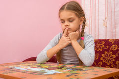 Child is thinking how to assemble a picture from puzzles Royalty Free Stock Image