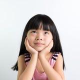 Child thinking. Little Asian girl child thinking over white background Stock Photography
