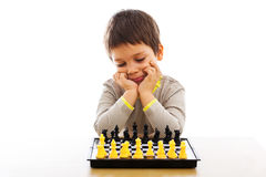 Child thinking about next move. Child playing chess, thinking about his next move Royalty Free Stock Photo