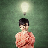 Child in thinking poses while looking at lamp Royalty Free Stock Photos